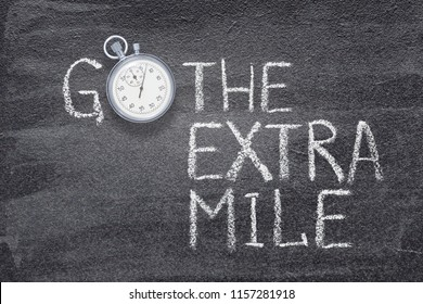 go the extra mile phrase written on chalkboard with vintage stopwatch used instead of O