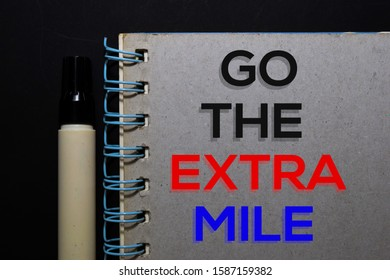Go The Extra Mile write on book. Top view isolated on black background.