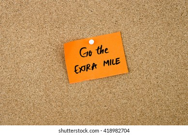 Go The Extra Mile written on orange paper note pinned on cork board with white thumbtacks, copy space available
