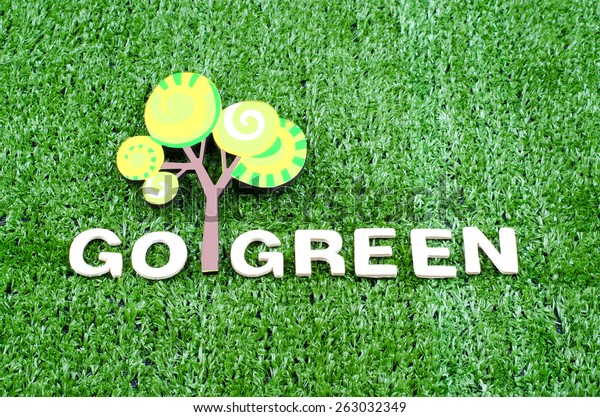 Go Green Concept with text and small tree on artificial grass