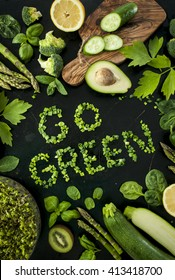 Go green concept - variety of green vegetables and fruit with natural lettering.  Black background. Avocado, basil, cucumber, lemon, lovage, sprouts, spinach, asparagus,  zucchini, kiwi, broccoli