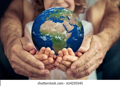 Go green! Family holding 3D planet in hands. Earth day holiday concept. Elements of this image furnished by NASA