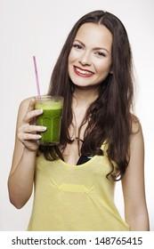 Go green. Young beautiful woman enjoying a healthy raw fruit vegetable juice. Studio shot.