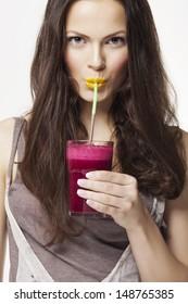 Go juicy. Young beautiful woman enjoying a healthy raw fruit vegetable juice. Studio shot.