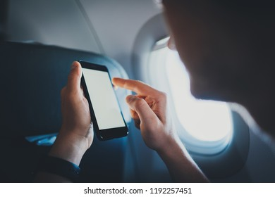 Go to the new adventures! Young hipster guy sitting in airplane and playing on smartphone, businessman using modern cellphone with empty screen copy space for text message or design, business travel