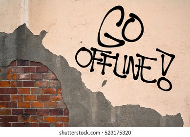 Go Offline - handwritten graffiti sprayed on the wall - danger of excessive social networking, reading emails, etc. Decision to turn off internet access. Prevention against addiction on technology