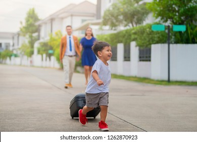 Go on an adventure! Cute little boy running and carrying a suitcase are going out of the house. Family preparing for travel, Vacation trip.