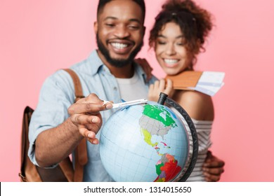 Go on an adventure. Happy couple preparing for journey, choosing route on pink background