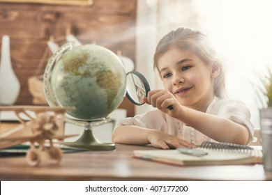 Go on an adventure! Happy cute child preparing for the journey. Pretty girl study the globe and choose a route of travel.
