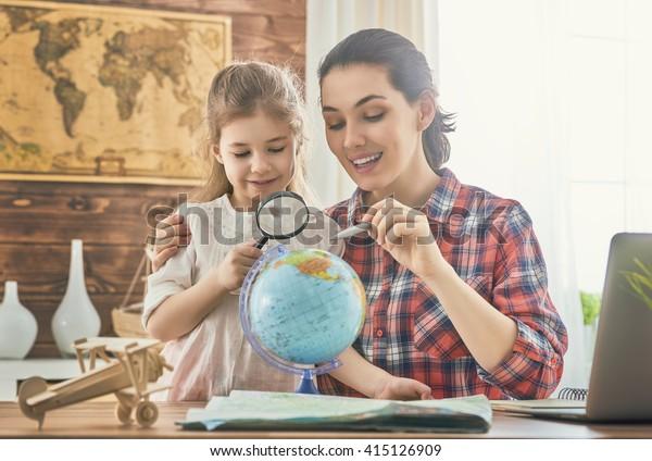 ¡Vamos a una aventura! Feliz familia preparándose para el viaje. Mamá e hija estudian el mapa y eligen una ruta de viaje.