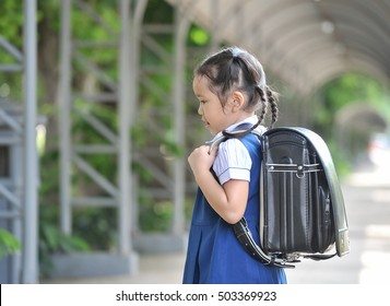 Go to school,Little Asian girl in school uniforms with backpack walking home little girl in traditional school dress at countryside,thailand.