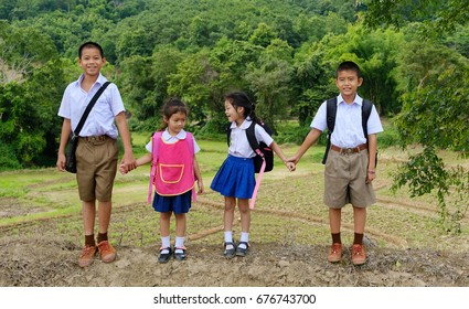 Go to school,Little poor Asian students in school uniforms carrying bags go to school ,little students in traditional school dress at countryside,thailand.