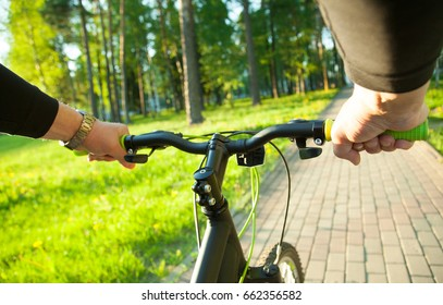 Go for a summer ride! Cyclist riding in a sunny summer park, first-person view