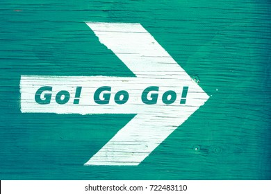 """Go! Go! Go!"" text written on a white directional arrow pointing towards right manually painted on a green blueish wooden signboard background. Photo framed horizontally."