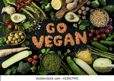 Go vegan concept with lettering. variety of fresh green organic vegetables & lentils on dark background. Vegan food concept.