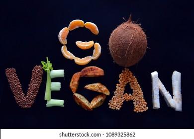 """Go vegan concept with lettering vegetables. variety of vegetables on dark background. Vegan food concept The word """"vegan"""" written with vegetables"""