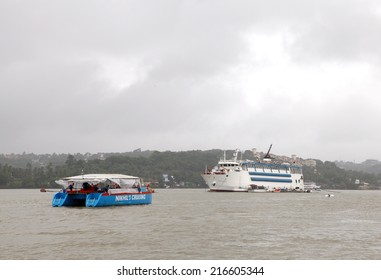 GOA, INDIA- AUGUST 10: A tourist boat and the Casinos Maharajah ship  in the Mandovi river Goa on August 10, 2014