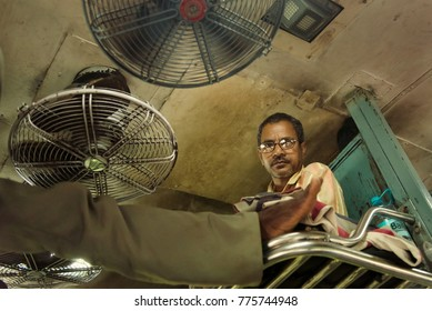 GOA, India - February 28, 2016: Male passengers of unreserved general class train. Low angle shot from inside. Indian railway transportation often noisy, crowded. Carriages are cooled with fans.