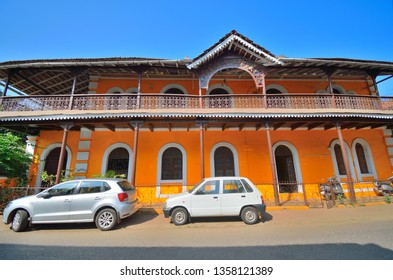 Goa, India - January 23, 2019: Cars parked in front of a yellow colored portuguse house in Panaji, Goa.