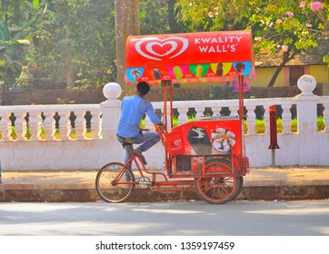 Goa, India - January 24, 2019: An ice cream seller waits for customers near his stand.