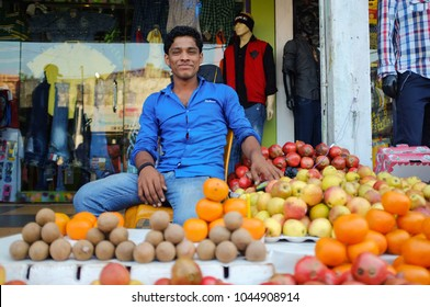 GOA, INDIA - JANUARY 27, 2015: Street fruit vendor sitting at fruit stand with a big smile.