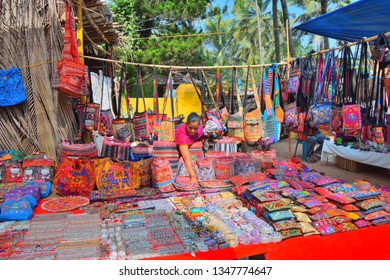 Goa, India - January 30, 2019: A woman selling wide variety of colorful handbags in a stall.
