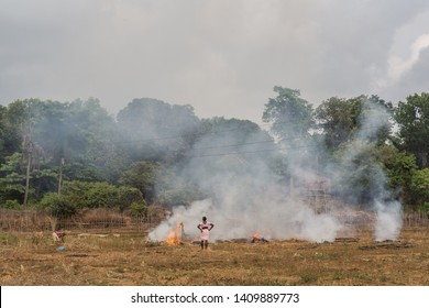 Goa / India - May 21 2019: An Indian female farmer doing stubble burning in a field on a late summer afternoon.