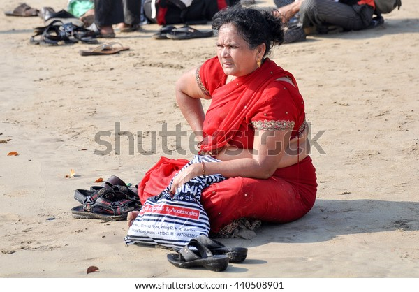 GOA,INDIA - March 13,2013:a woman in a red Sari sitting on the sand at the Baga beach in North Goa