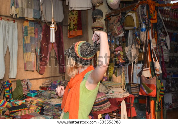 GOA,INDIA - NOVEMBER 12,2016:woman trying on a hat made of hemp at the store on the Arambol beach.