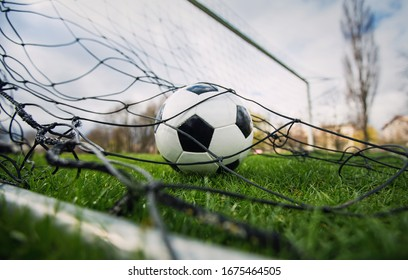 Goal concept as a soccer ball enters the gate and hits the net. Football championship background, spring outdoors tournaments on the stadium. Healthy sports activity and games.