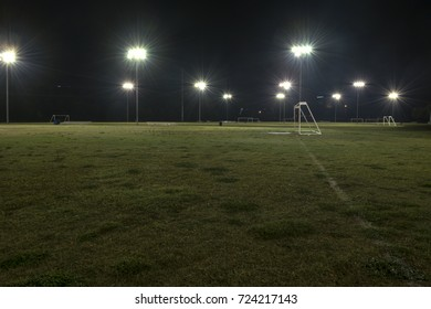 Goal and empty soccer fields at night with the lights illuminating the green grass and reflecting off water drops from a recent rain.