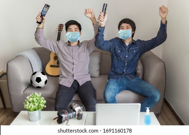 Goal! Happy soccer fans sitting on sofa wearing protective mask and cheering for a football team watching sports TV. Working from home concept.