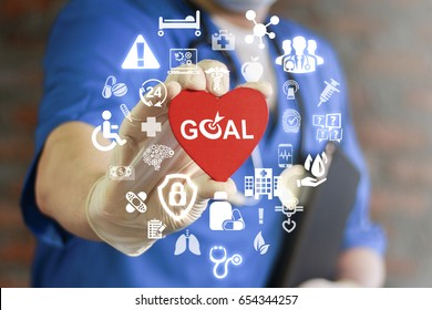 GOAL Health Care. Target in medicine treatment. Medical Success Strategy Plan Concept. Purpose achievement in hospital work. Doctor offers heart with goals icon on virtual screen. Healthy life style.