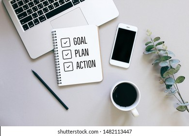 Goal, plan and action for 2020 on flat lay photo of workspace desk with smartphone, coffee, laptop and notebook with copy space background, minimal style and mockup concept