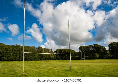 Goal post in a mowed grass playing field on a sunny summer day
