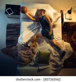Goal. Top view of young professional basketball player sleeping at his bedroom in sportwear with ball. Loving his sport even more than comfort, playing match even if resting. Action, motion, humor.
