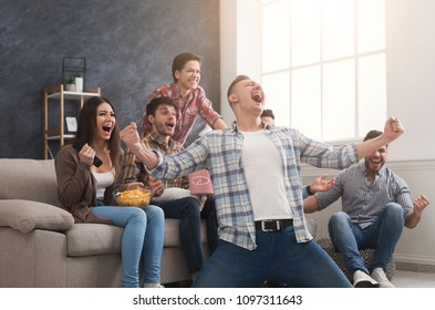 Goal. Very excited friends having fun by watching football match and eating at home, indoors. Friendship, leasure, rest, home party concept