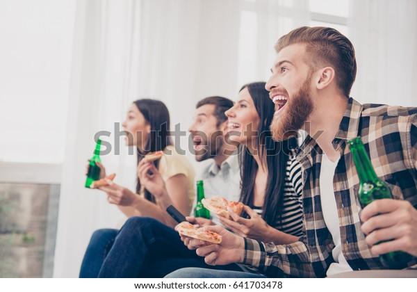 Ziel! Sehr aufgeregte Jugend macht Spaß beim Fußballspiel, Bier trinken, Pizza zu Hause zu Hause essen