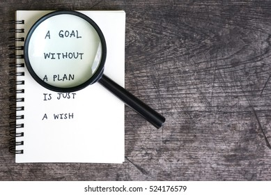 a goal without a plan is just a wish motivational handwriting on a open notebook  with magnifying glass