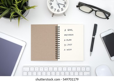 Goal without a plan is just a wish, quote business in open notebook with pen, eye glasses, smart phone, tablet, keyboard, mouse, computer, alarm clock and small plant over office table background