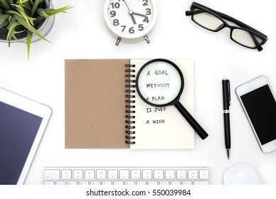 Goal without a plan is just a wish, quote business in office table with open notebook, magnifying glass, pen, eye glasses, smart phone, tablet, computer, alarm clock and small plant over white desk