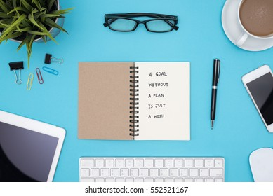 a goal without a plan is just a wish motivational handwriting on spiral notebook with computer, office supplies, eye glasses and coffee over blue desk table, Top view with copy space
