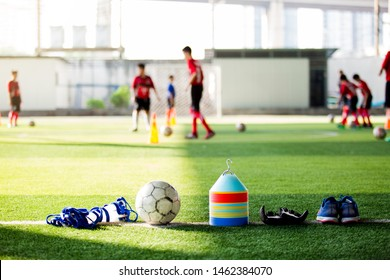 Goalkeeper gloves and football on green artificial turf. Football and soccer training equipment on green artificial turf with blurry player training background. Soccer Academy.