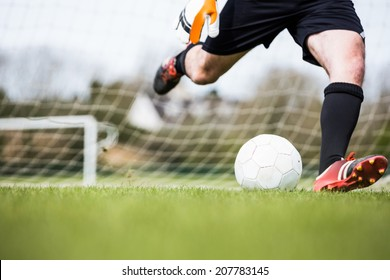 Goalkeeper kicking ball away from goal on a clear day