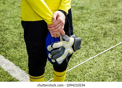 Goalkeeper standing on field near the gate on background green grass closeup. Goalkeeper took off his gloves