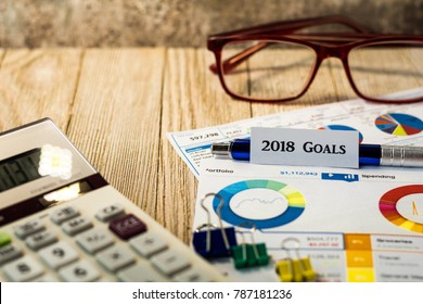 Goals for 2018 motivational concept with charts and graphs and calculator on wooden board