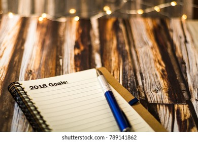 Goals for 2018 on a notebook motivational concept on dark wood planks for vintage retro look