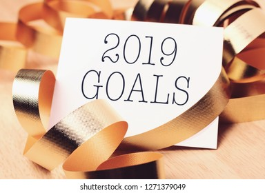 Goals 2019 with gold decoration. Discover how setting goals can bring more happiness in your life.