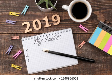 Goals for 2019. text in notebook. with pen and coffee on a brown wooden background. view from above