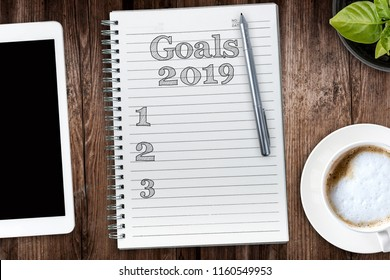 Goals in 2019. View from the top of the flat lying objects on the table and in the notebook recorded goals for 2019. Filtered in instagram style.